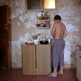 RUSSIA / St.Petersburg / July 2007 / A boy cooks in his dilapidated communal kitchen. Basically, every household in a communal flat should have a cooking table and a cupboard of their own. 