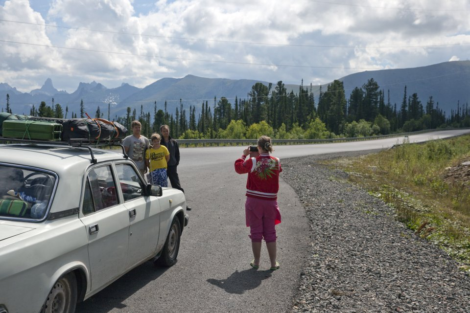 Tourists take a picture during a stop on the M-54 - basically the only road that connects Tuva with the rest of Russia. The rugged Yergak-Targak-Taiga ridge - part of Sayan Mountains - is visible in the background. Before Tuva joined the Soviet Union in 1944, this ridge formed the natural border between the two countries.