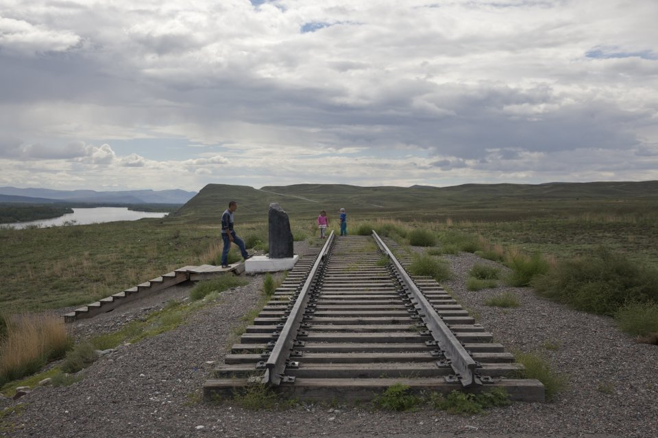 "A father and his kids inspect the ""first"" rail track section and a foundation stone outside the Tuvan capital Kyzyl where its future railway station is supposed to sit. Tuva had never had any railways. A rail link that would connect Tuva with the southern branch of the Transsiberian Railway has been designed and approved by the Russian government in 2007 but the project has never really taken off ever since due to doubts about its cost-effectiveness."
