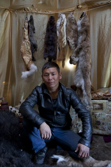Saidash Kol, 28, a deer farmer and hunter from the Todzha area (northeastern Tuva), poses for picture in his tent he and his workers have built for the yearly Naadym farmers' fest. He also owns a fishery, a cafe and a hotel in his village. Once nomadic deer farmers, Todzha Tuvans no longer live in this kind of tents, preferring village homes, but some of them still know how to build a tent for special occasions such as this Naadym fest. Deer were not brought over though for they pasture deep in the forest during this time of year and their respiratory systems are not used to dusty steppes. Tos-Bulak, Tuva, Russia.