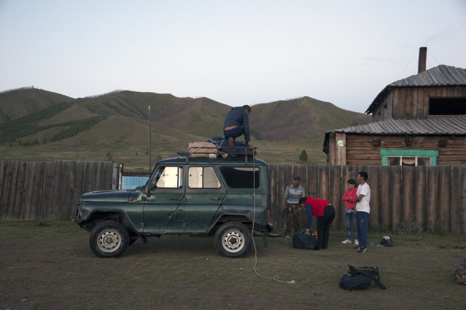 Ertine Bandan (on the roof of the vehicle) unloads the luggage near the home of Bayir-Kys Banchyk - director of the village hall (in red sleeveless jacket) whom he gave a ride - in front of her home in Kachyk, a remote and hard-to-get village near the Mongolian border. The isolated Kachyk sumon (community) has about 300 residents, partly living in the village itself, partly - at nomadic stations in the surrounding valleys. According to Moscow-based sociologist Artemiy Pozanenko who has been studying spacially isolated communities in the post-Soviet world, they tend to be more cohesive and self-sustainable because in part of unlimited access to natural resources around them and absence of regulatory authorities.