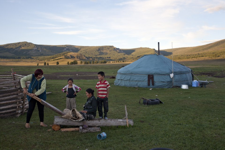 Bayir-Kys Banchyk and Valentina Sambyr demonstrate the traditional way to tan cowhide which is then used to make shoes, as youngsters look on. Such crafts survive only in such isolated communities as this one in Kachyk river valley in southeastern Tuva